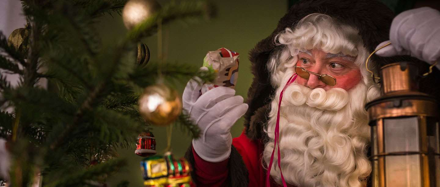 Father Christmas holds up a gift