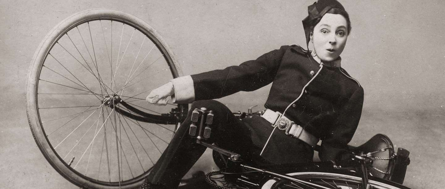 Black and white photograph of Vesta Tilley dressed as a policeman and falling off a bicycle