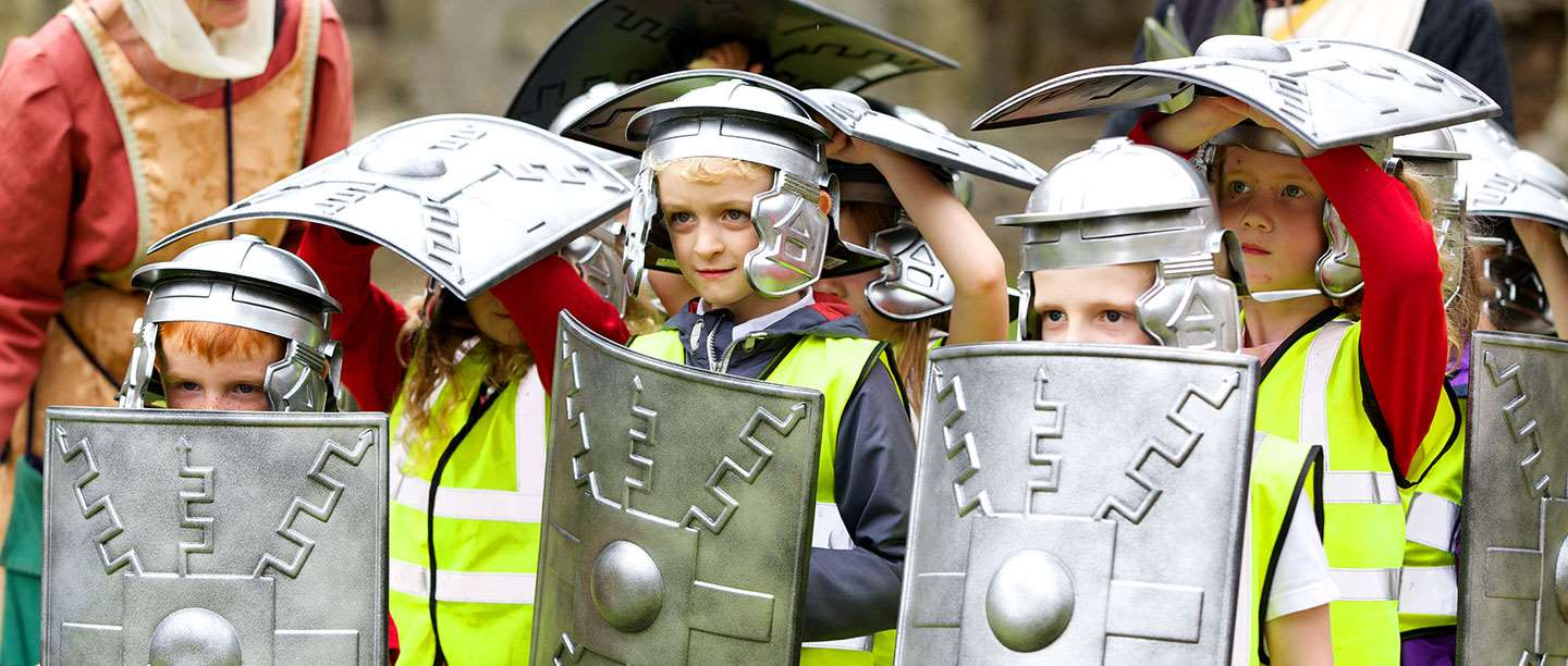 Students dressed in Roman helmets and holding Roman shields in a protective shell formation