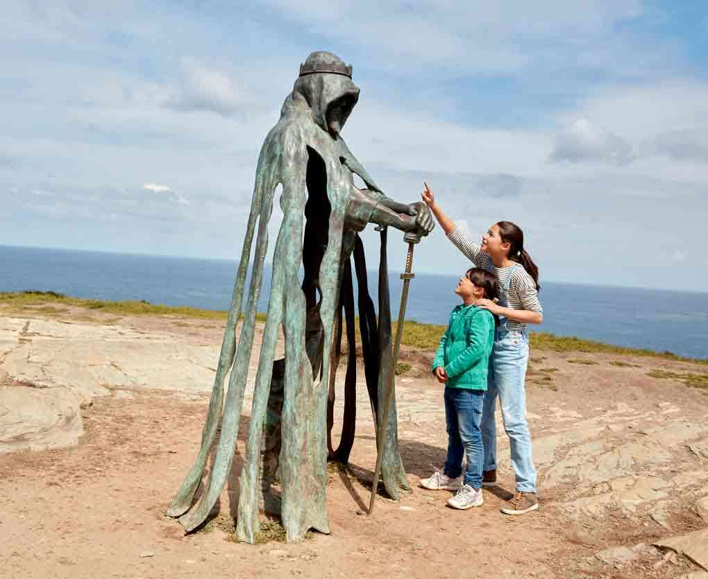 Children looking at the Gallos statue at Tintagel in Cornwall