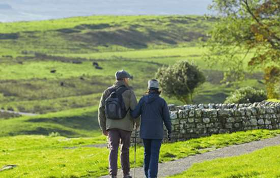 Image: couple walking next to Hadrian's Wall