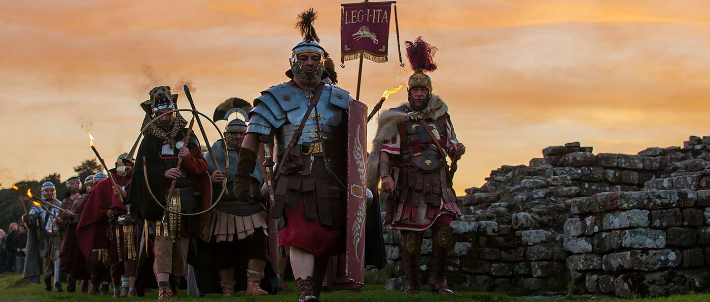 Image: Roman re-enactors marching by Hadrian's Wall at sunset