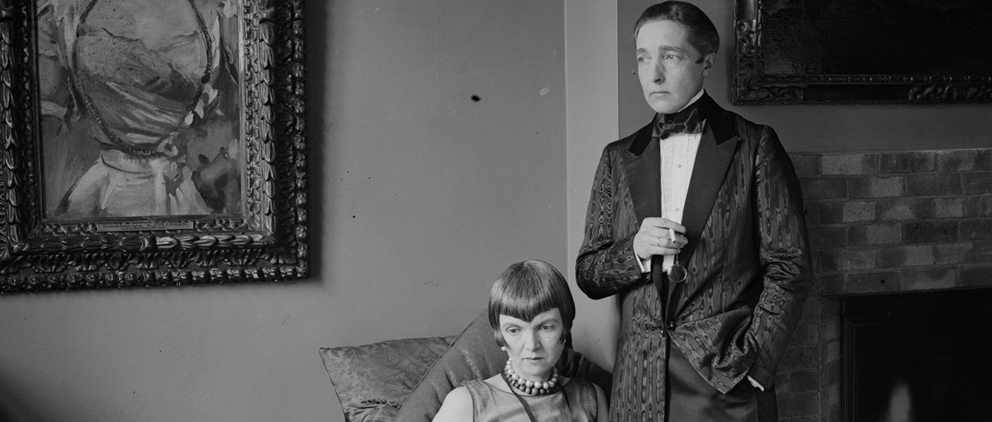 Black and white photograph of Radclyffe Hall in men's dinner jacket standing beside Lady Una Troubridge, seated and wearing evening dress with pearl necklace