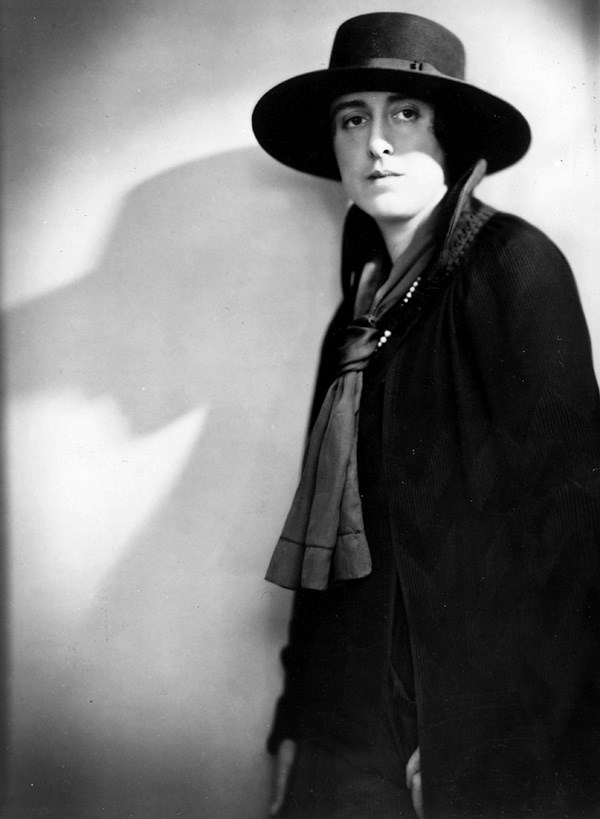 Black and white photograph of Vita Sackville-West standing at right of frame, wearing dark cloak and broad-rimmed hat