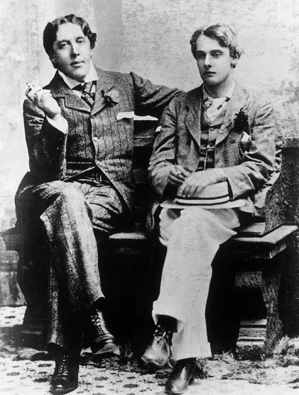 Black and white photograph of Oscar Wilde and Lord Alfred Douglas sitting next each other, Wilde smoking