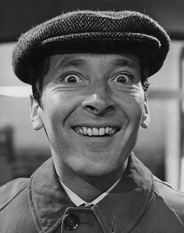 Black and white photograph of Kenneth Williams grinning broadly at camera