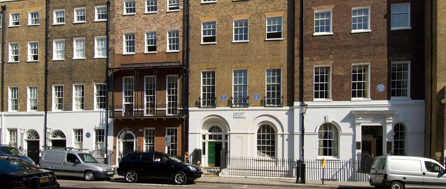 View of terraced brick housing with four blue plaques visible