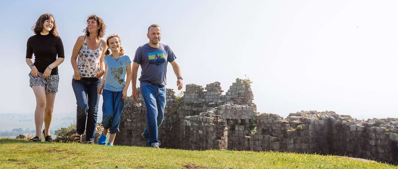 A family walk past a historic ruin