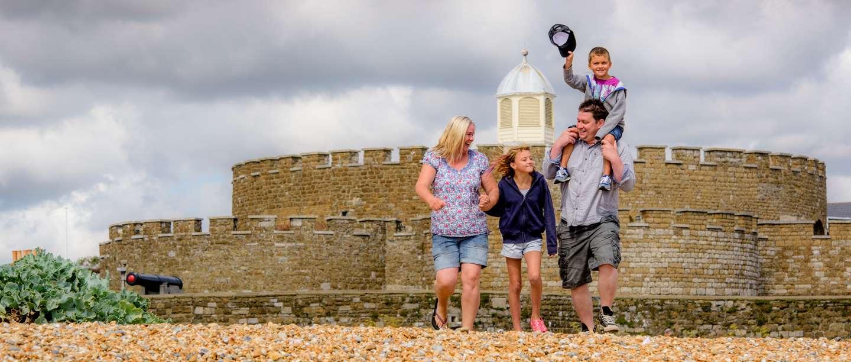 Image: family walking on beach near Deal Castle