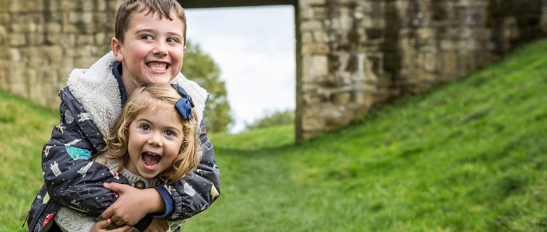 A boy hugs a girl at Warkworth Castle
