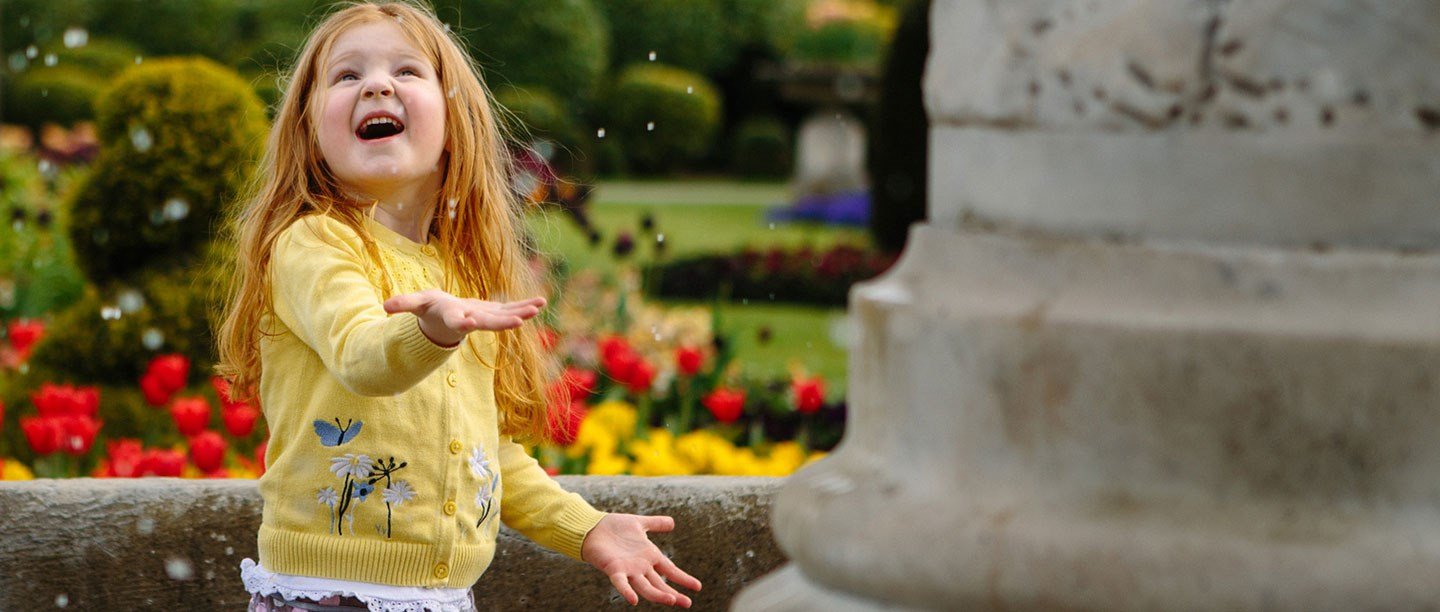 A young girl smiles besides a fountain with tulips in the background