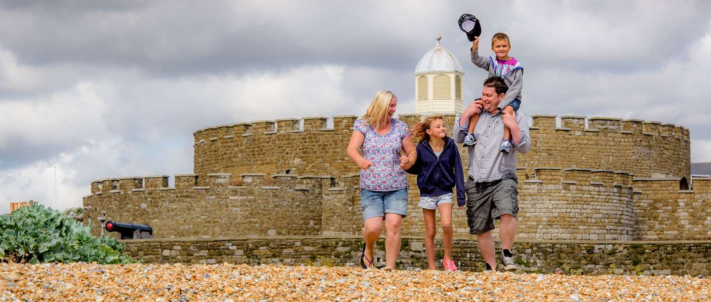 A family walk ahead of a medieval castle in summer