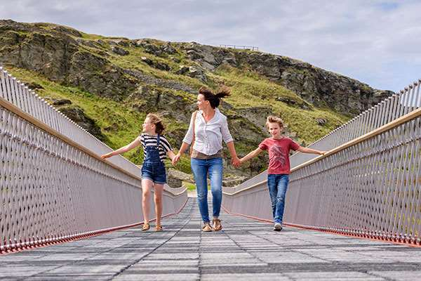 Family crossing Tintagel Castle Bridge