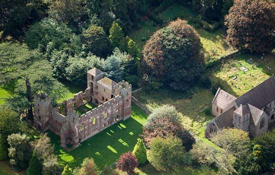 Aerial view of Acton Burnell Castle ruins alongside 13th century medieval St Mary's Church set amongst a rich planting of trees
