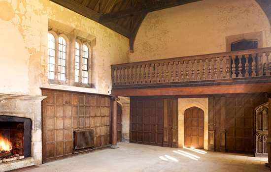 Interior view of room with fireplace, wood panelled walls and gallery at Apethorpe Palace