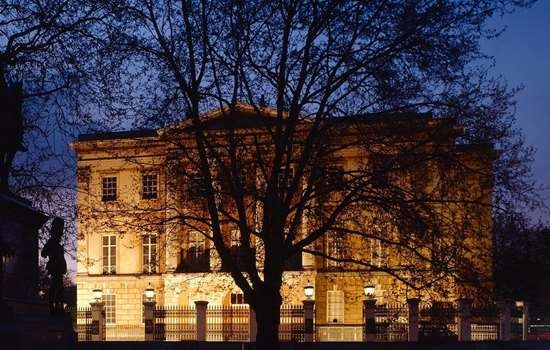 View from the south east of Apsley House floodlit at night with silhoette of the Wellington Statue to the left