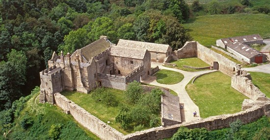 Aerial view of the substantial remains of Aydon Castle perched on the edge of scarp above Cor Burn