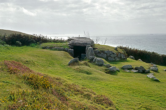 The stone entrance to Bants Carn with the ocean in the background