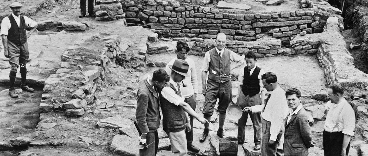 Black and white photograph showing archaeologists grouped around a piece of Roman stone