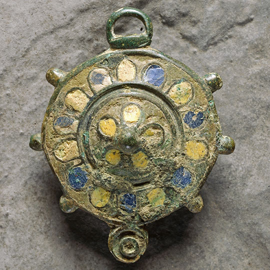 An enamelled bronze disc brooch found at Birdoswald