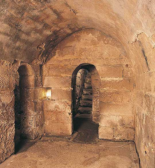 Interior of Hexham crypt with view through narrow arched doorway to steps leading up