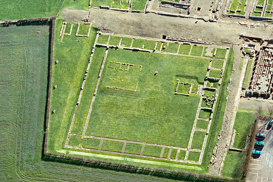 The courtyard building, known as Site XI, Corbridge Roman Town, its clear stone wall footings offset by verdant green lawn