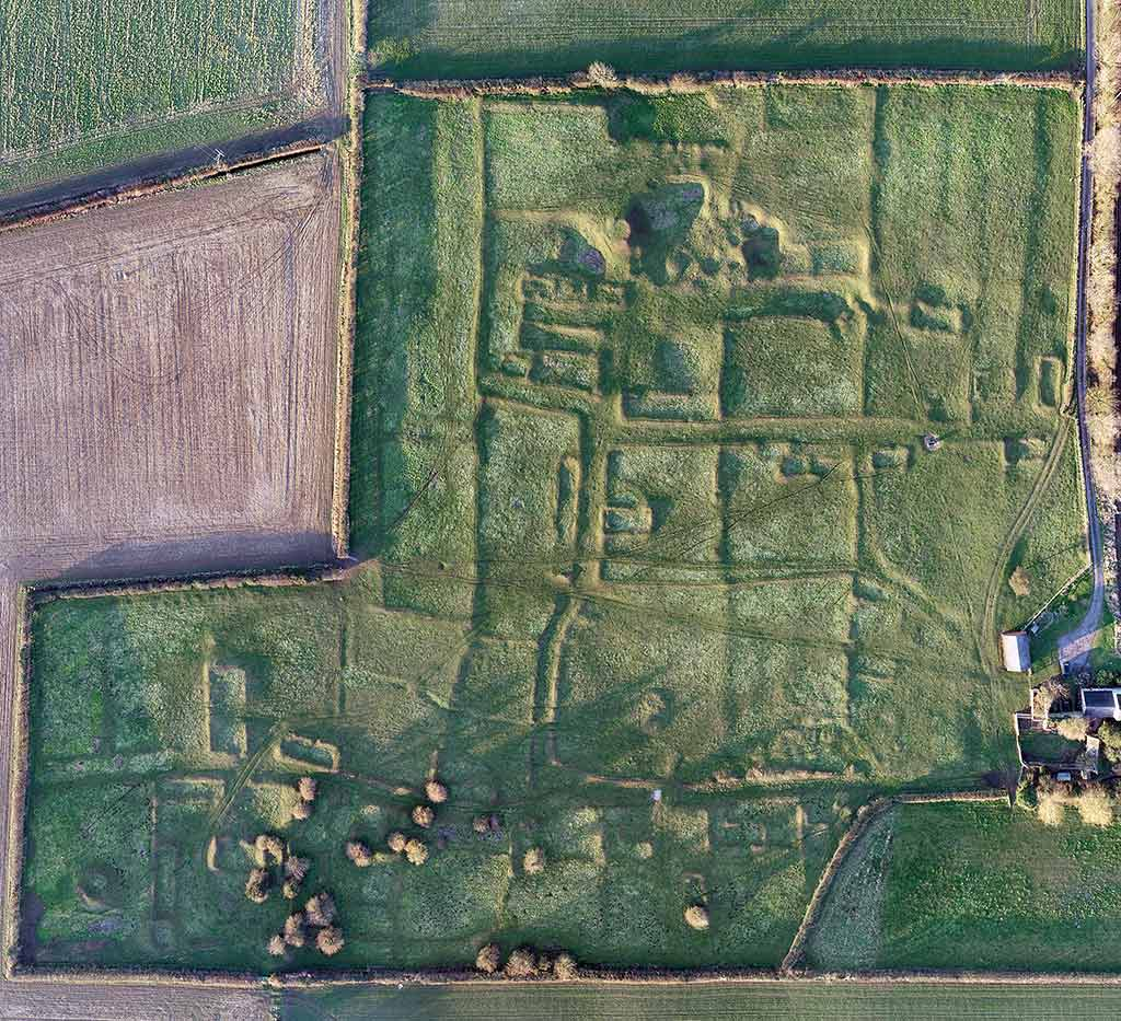 This vertical aerial photo of the village, taken in 2019, shows the medieval earthworks exceptionally clearly