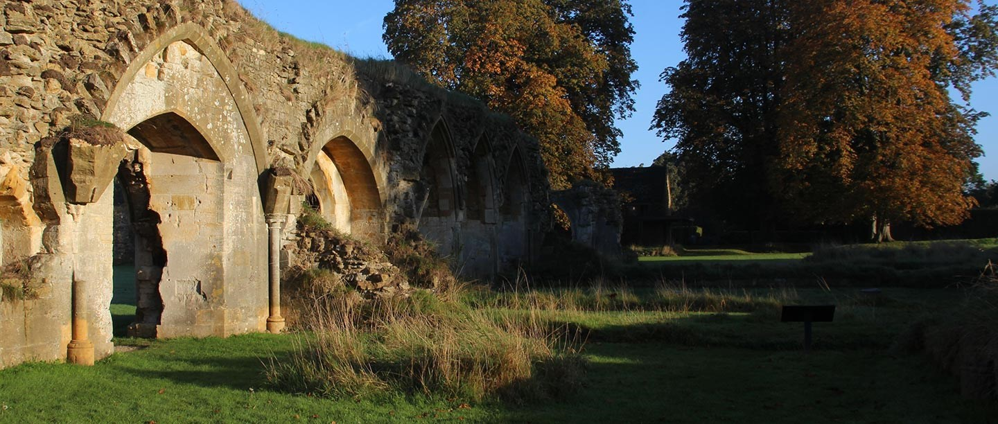 Photograph of Hailes Abbey ruins in early morning sunlight set within autumnal Cotswolds landscape