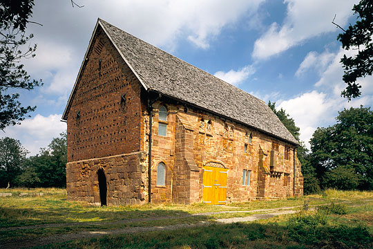 The north barn of Halesowen Abbey, incorporating medieval masonry and timbers, its yellow stone glowing in the warm sunshine