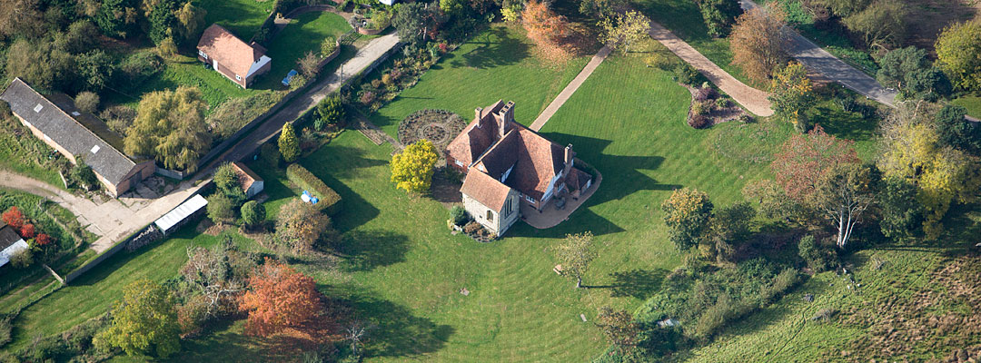 Aerial view of Hornes Place Chapel and the attached manor house in a mature garden landscape