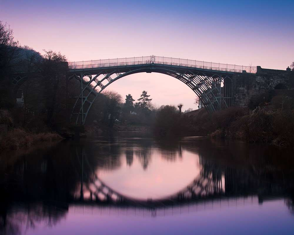 The Iron Bridge at night against a purple sky