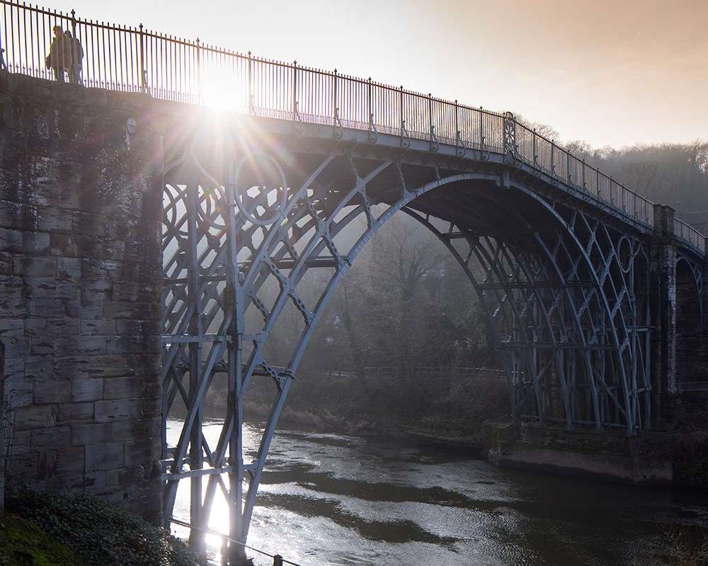 Visitor walking across the Iron Bridge with sun shining through the railings