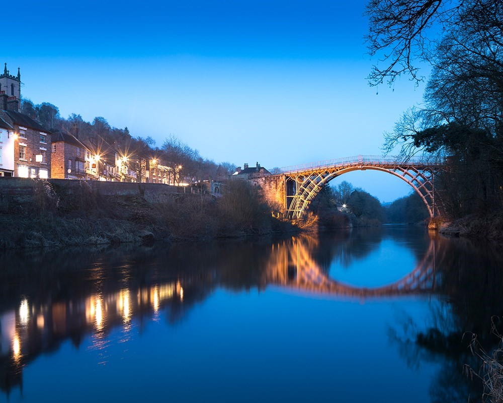 The Iron Bridge lit up against a blue nighttime sky