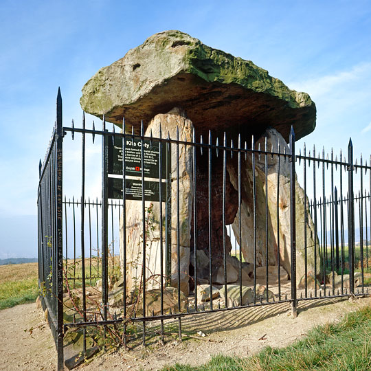 The burial chamber at Kits Coty House, surrounded by a protective black iron railing enclosure