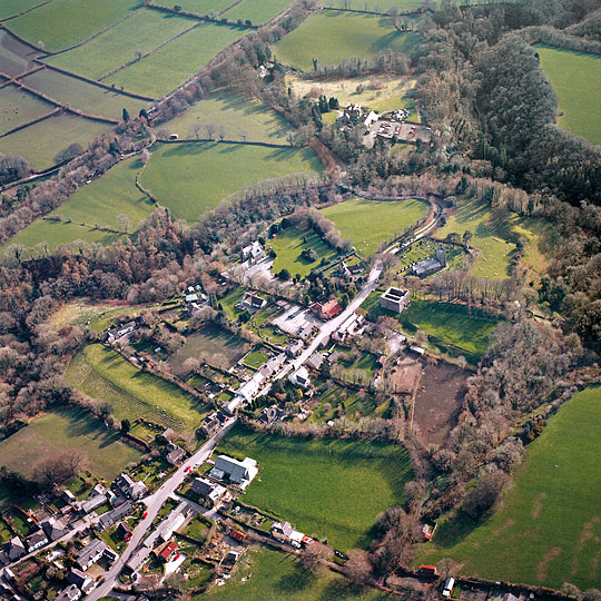 Aerial photograph of Lydford from the north-east, the narrow road running through the village past the tower