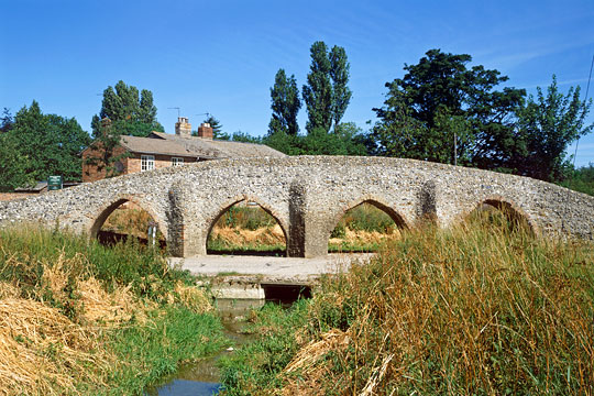 The 15th century bridge from the south with stream in foreground and cottage behind