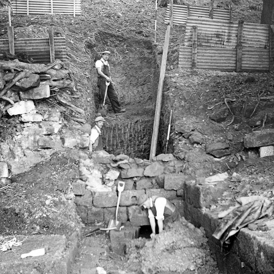 Black and white photograph of excavations at Mount Grace priory in 1957, two diggers in flat caps, waistcoats and rolled up sleeves