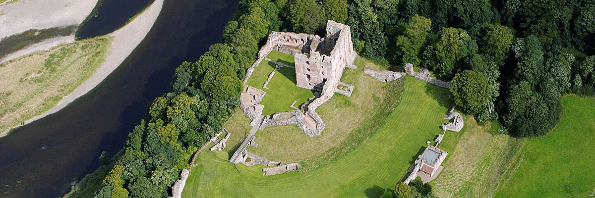 Norham Castle, dominated by its great tower, stands in a commanding defensive position beside the river Tweed