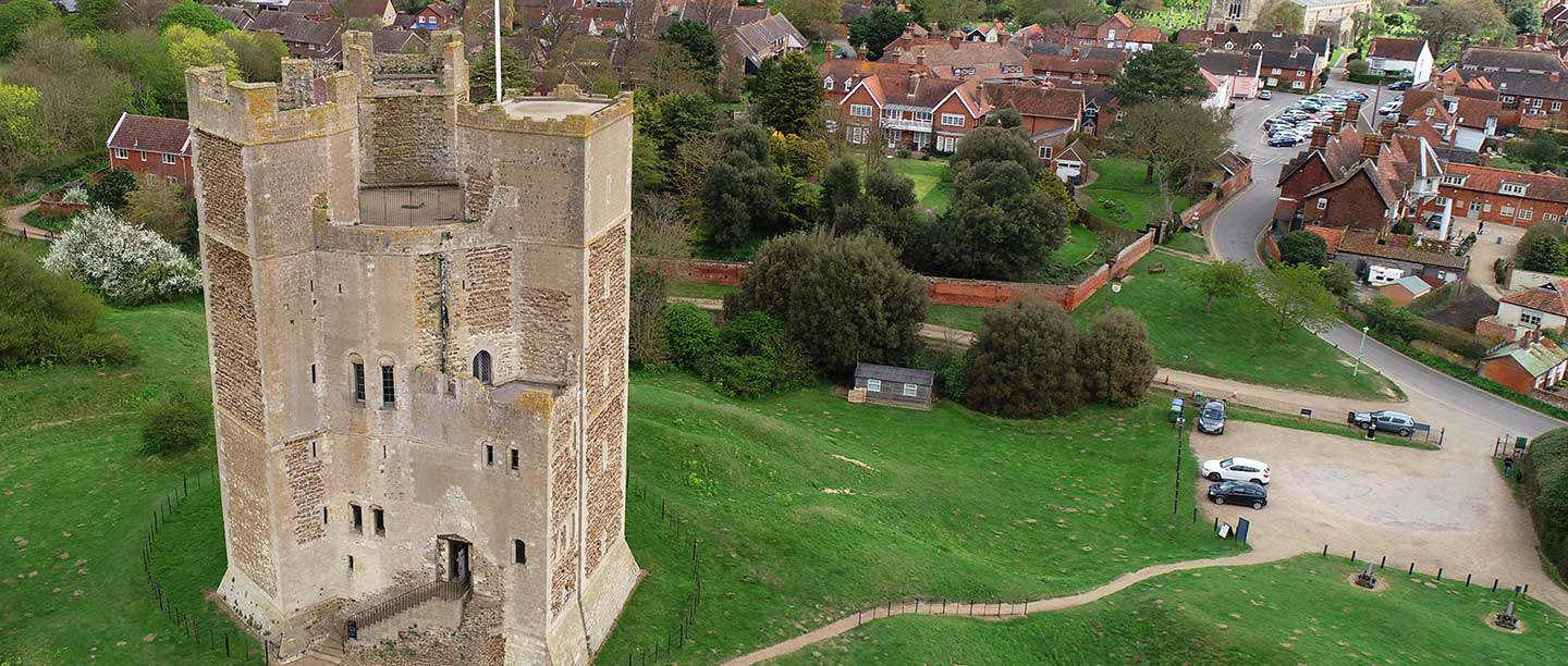 A drone shot of Orford Castle taken from almost level with the top parapets; the castle has beige stone and is on a grass hump.