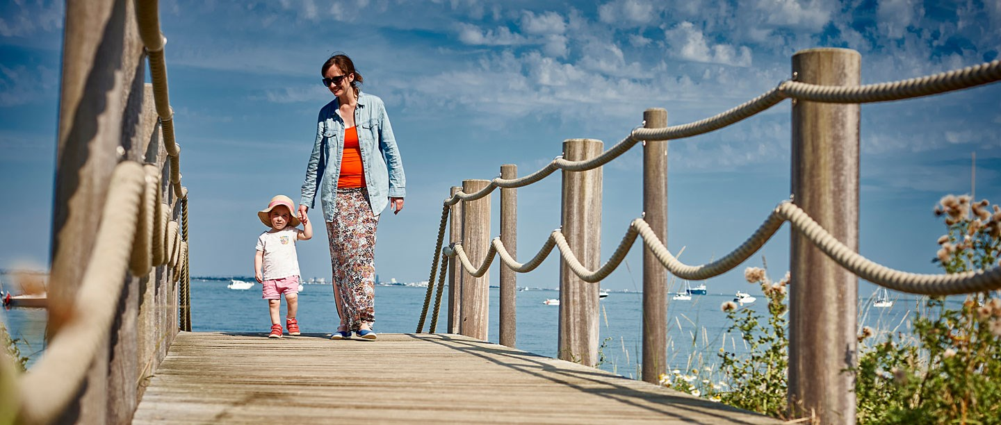 A parent and child walking on the beach at Osborne