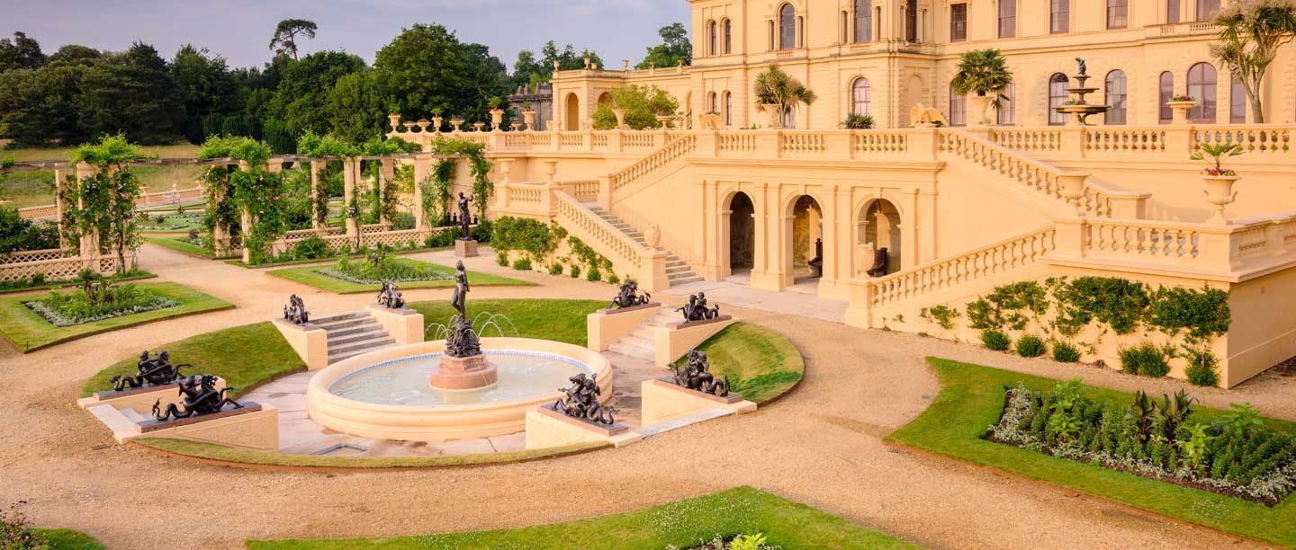 The terraces of Osborne House, peach in colour, with planted gardens and a fountain.