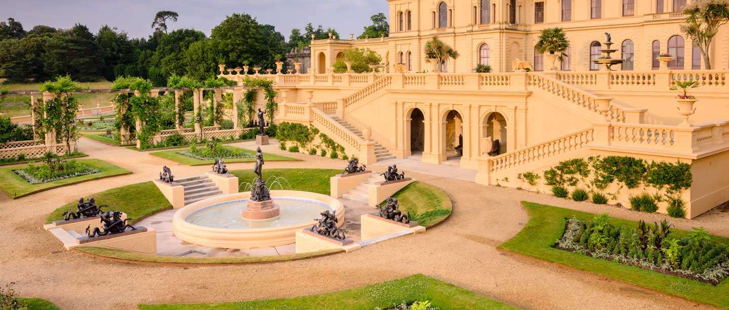 The terraces of Osborne House, peach in colour, with planted gardens and a fountain