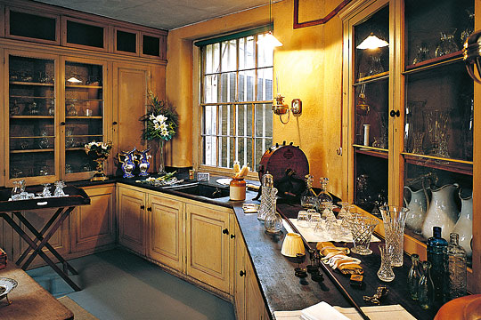One of the Table Deckers' Rooms at Osborne, with glassware, crockery and cutlery on worktops and in cupboards plus a valet tray laid out