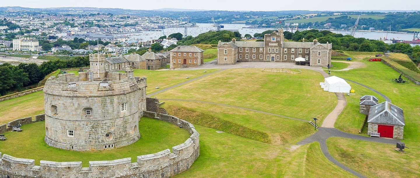 A view of the castle from above showing a grassy area and grey castle and walls.