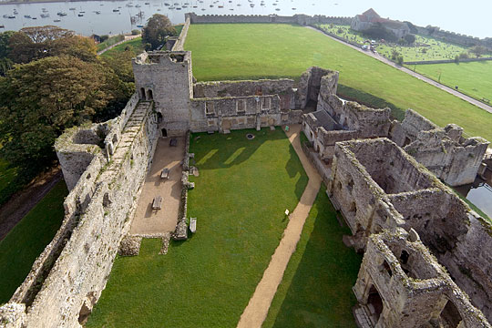 View of the outer bailey of Portchester Castle from the great tower, boats in the estuary beyond
