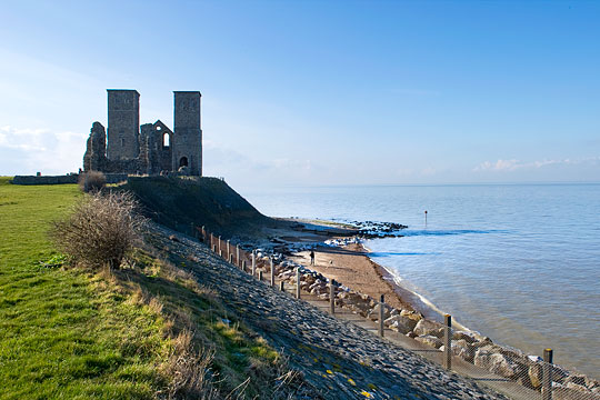 A view of the imposing towers of the medieval church at Reculver, standing on the edge of a low cliff above the rocky shore