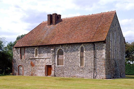 St Johns Commandery with flint walls and red tiled roof with chimneys