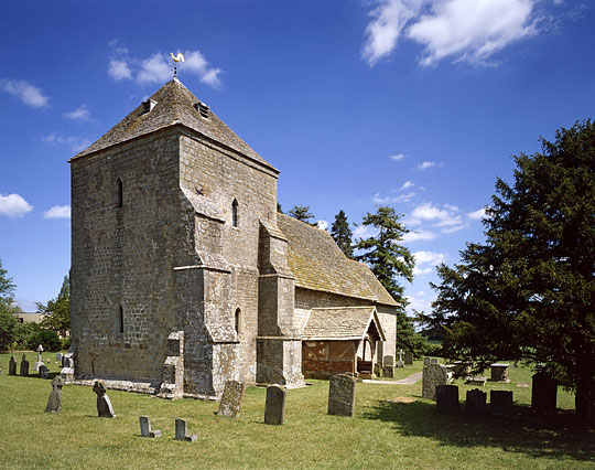 St Marys, Kempley, in full sunshine with grave head stones in foreground
