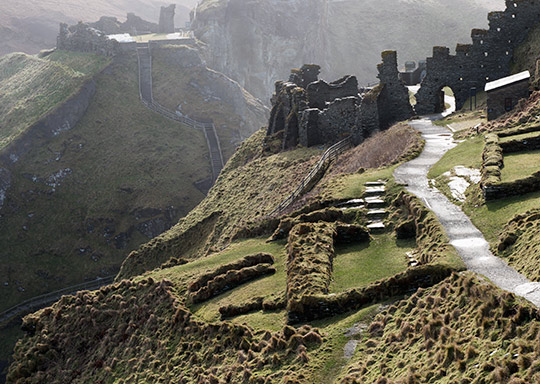 The remains of Tintagel Castle on Tintagel island, looking towards the mainland. There is a path running through it. To the left of the path are some of the remains of the 5th- to 7th-century settlement
