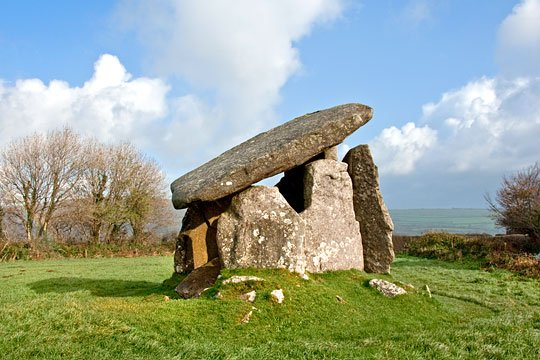 Trethevy Quoit stands impressively in its small pasture field with rolling hills beyond